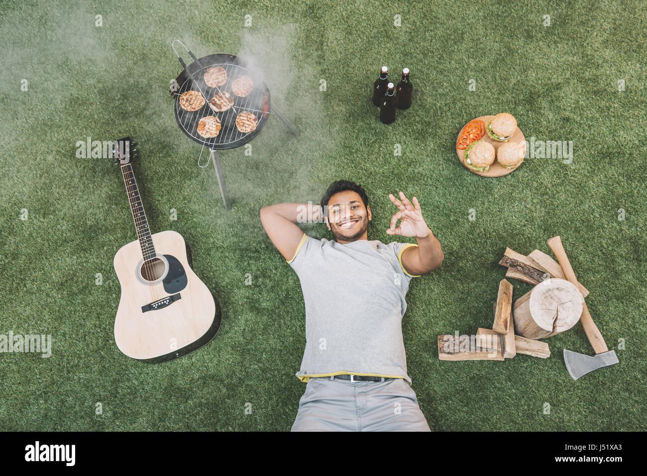 Draufsicht der glückliche junge Mann ok Anzeichen mit Gitarre und Nahrung für Picknick auf dem Rasen liegend Stockbild