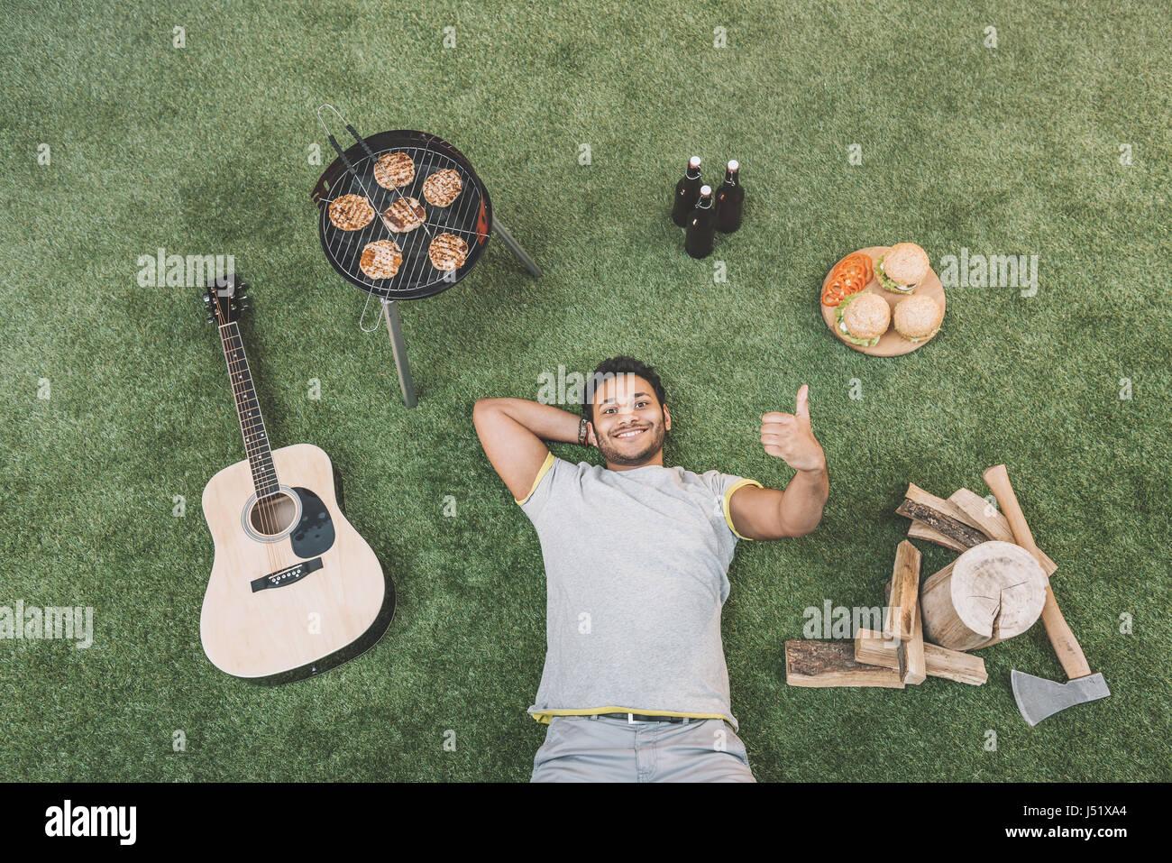Draufsicht der glücklich junger Mann Daumen auftauchen und ruht auf dem Rasen mit Gitarre und Nahrung für Stockbild