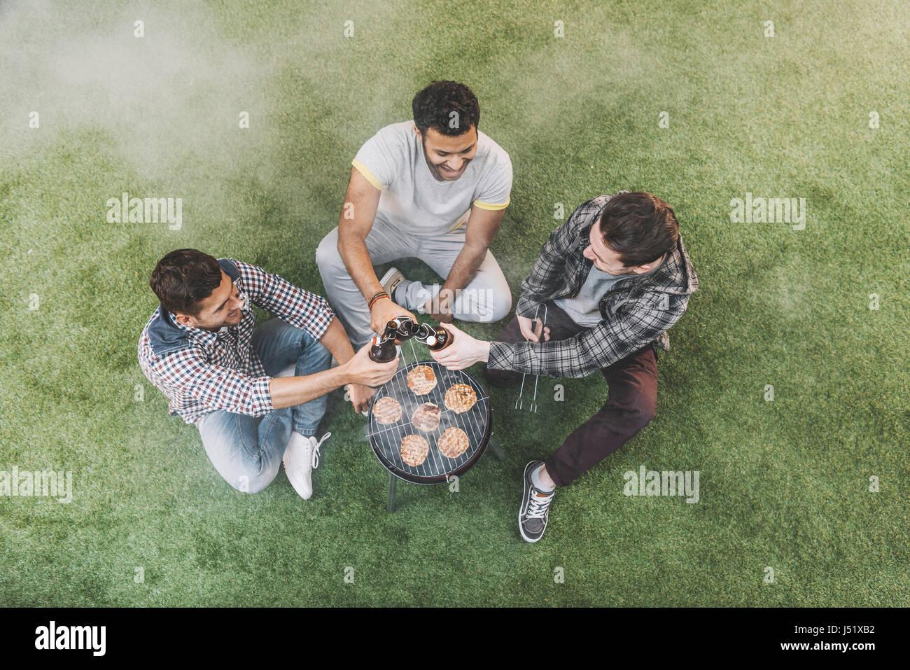 Draufsicht der jungen Männer auf dem Rasen sitzen und trinken Bier beim Grillen von Fleisch Stockbild