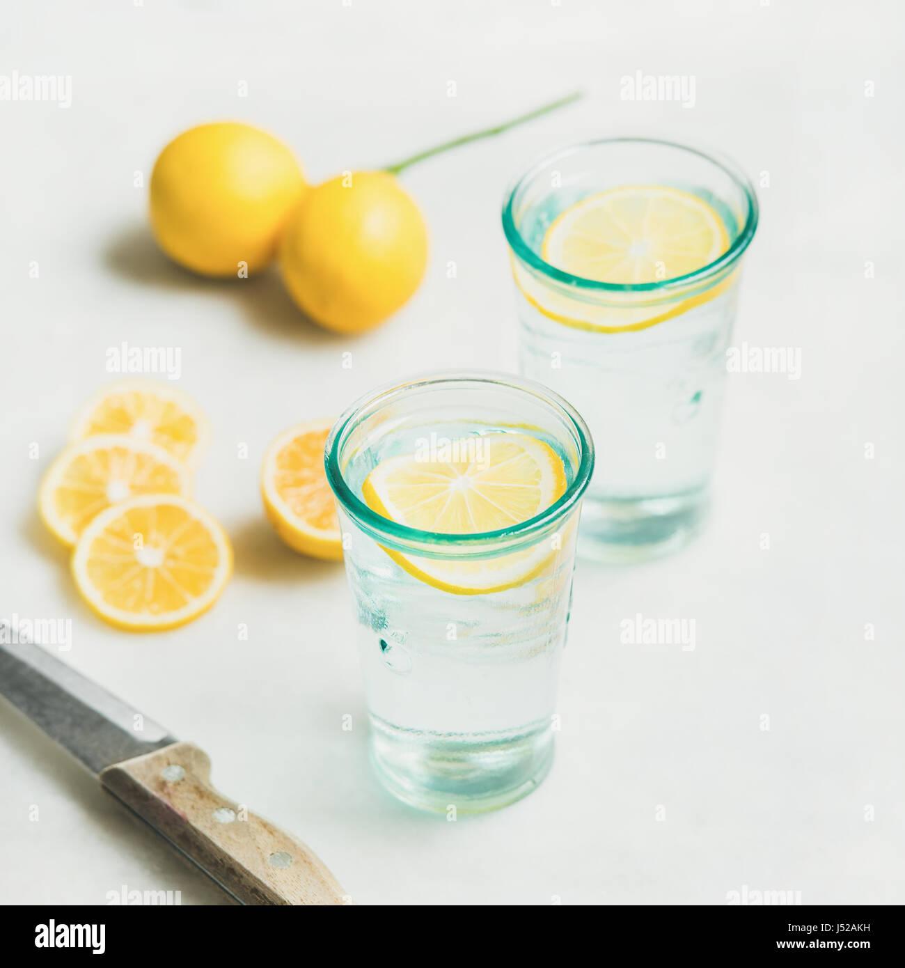Morgen Detox Zitrone Wasser in Gläsern und frischen Zitronen über Marmor Hintergrund, Tiefenschärfe, Stockbild