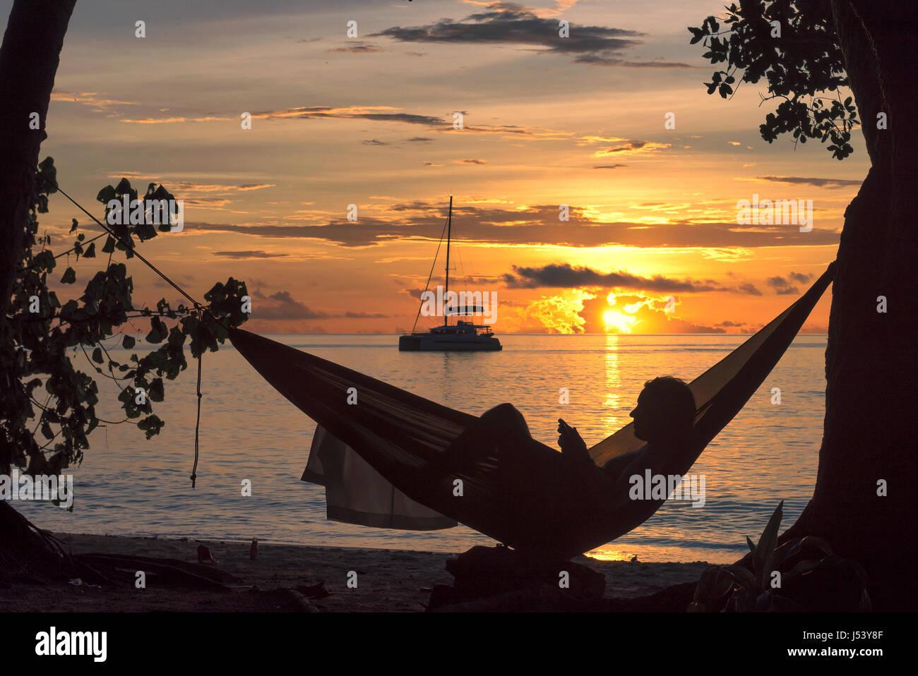 Strandurlaub, Silhouette einer Frau in Hängematte bei Sonnenuntergang auf der tropischen Insel lesen. Stockbild