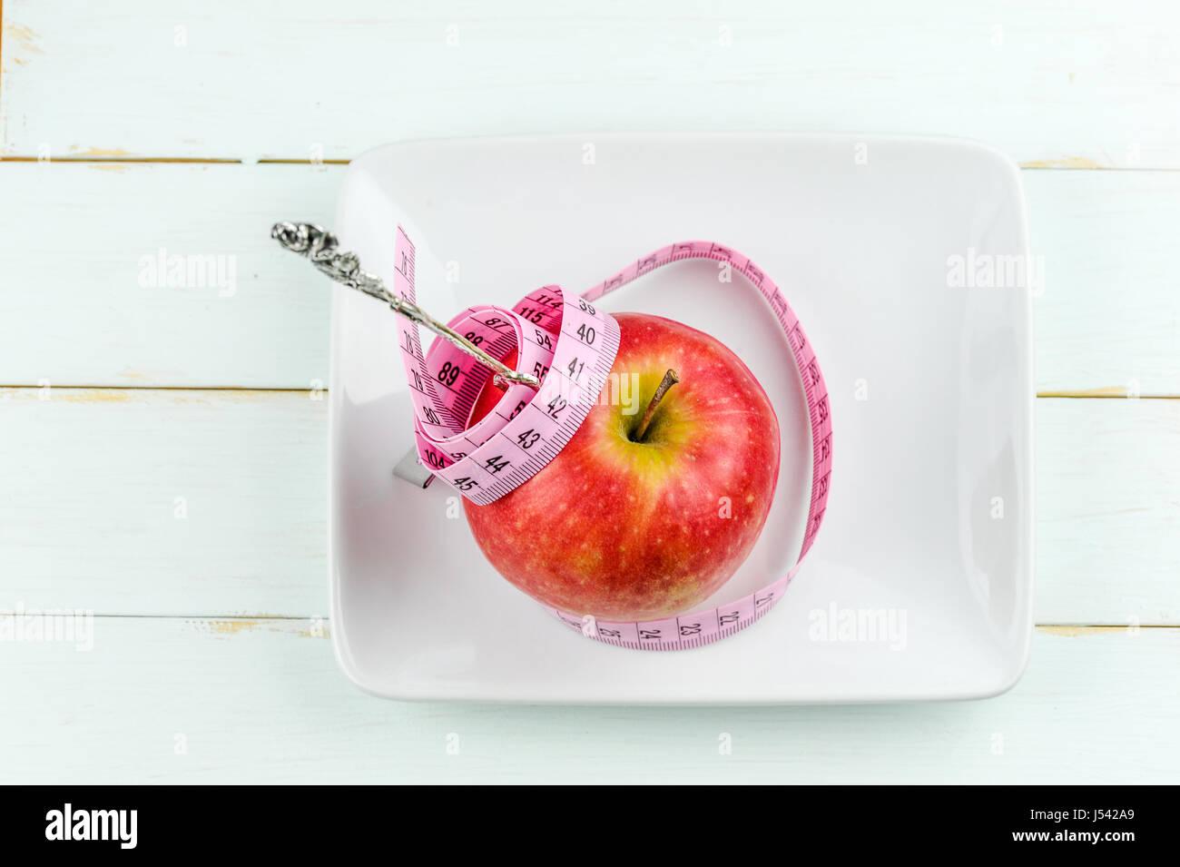 roter Apfel mit Maßband und Gabel auf hölzernen Hintergrund, Diät-Konzept Stockbild