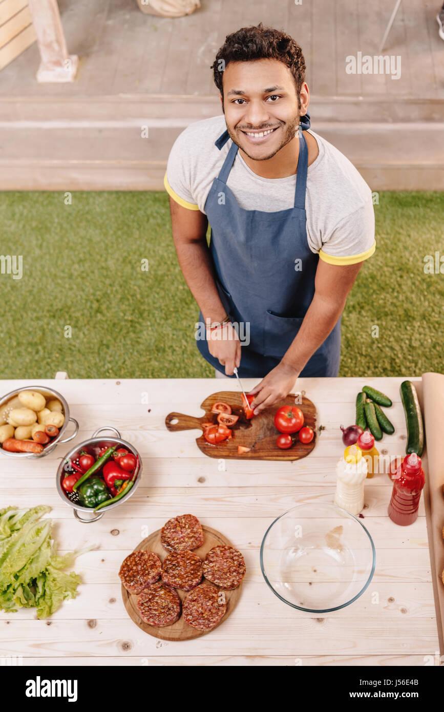 Menschen machen Burger und schneiden rote Tomaten im freien Stockbild