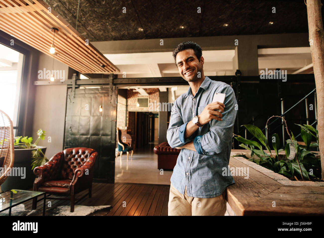 Porträt von hübscher junger Mann entspannend in modernen Büro Blick in die Kamera und lächelnd. Stockbild