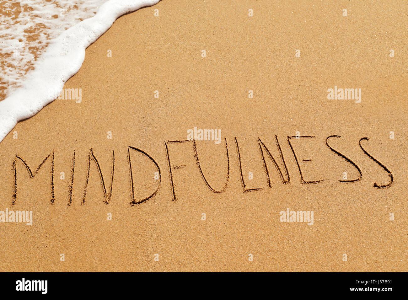 das Wort Achtsamkeit, geschrieben in den Sand des Strandes Stockfoto