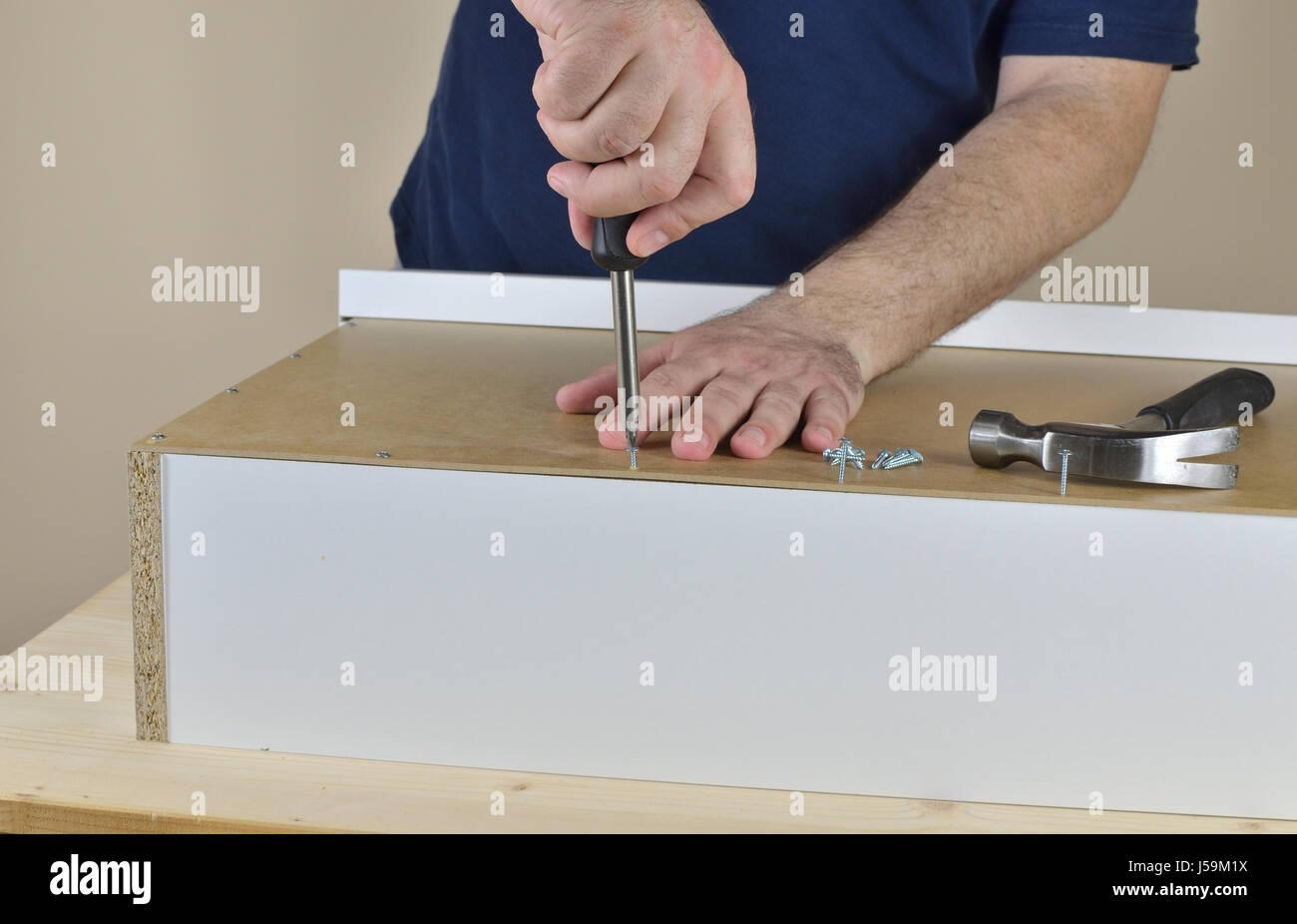 Hände des Mannes ein Holz Schrauben Schraube in eine Schublade ...