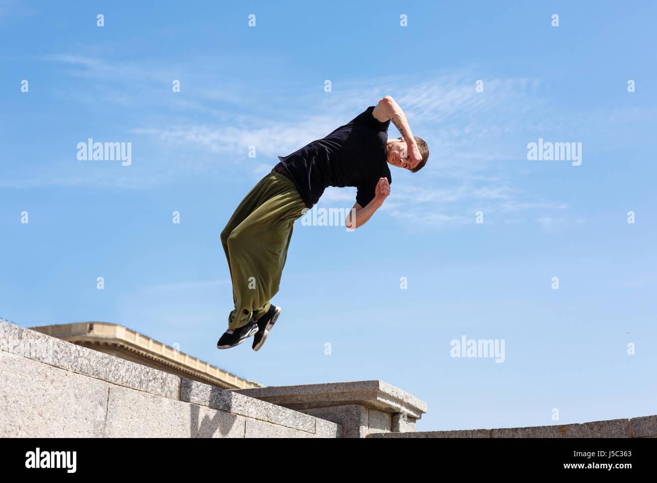 Junge Mann tut ein Back flip mit einer Umdrehung. Parkour im urbanen Raum. Sport in der Stadt. Sportliche Aktivität. Stockbild