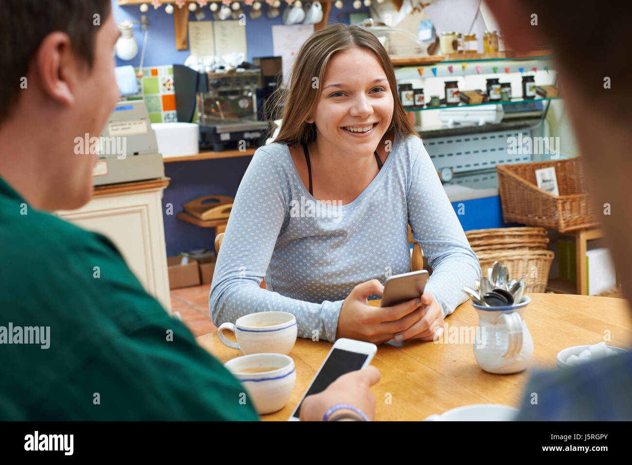 Gruppe von Jugendlichen Freunde treffen im Cafe und Benutzung von Mobiltelefonen Stockbild