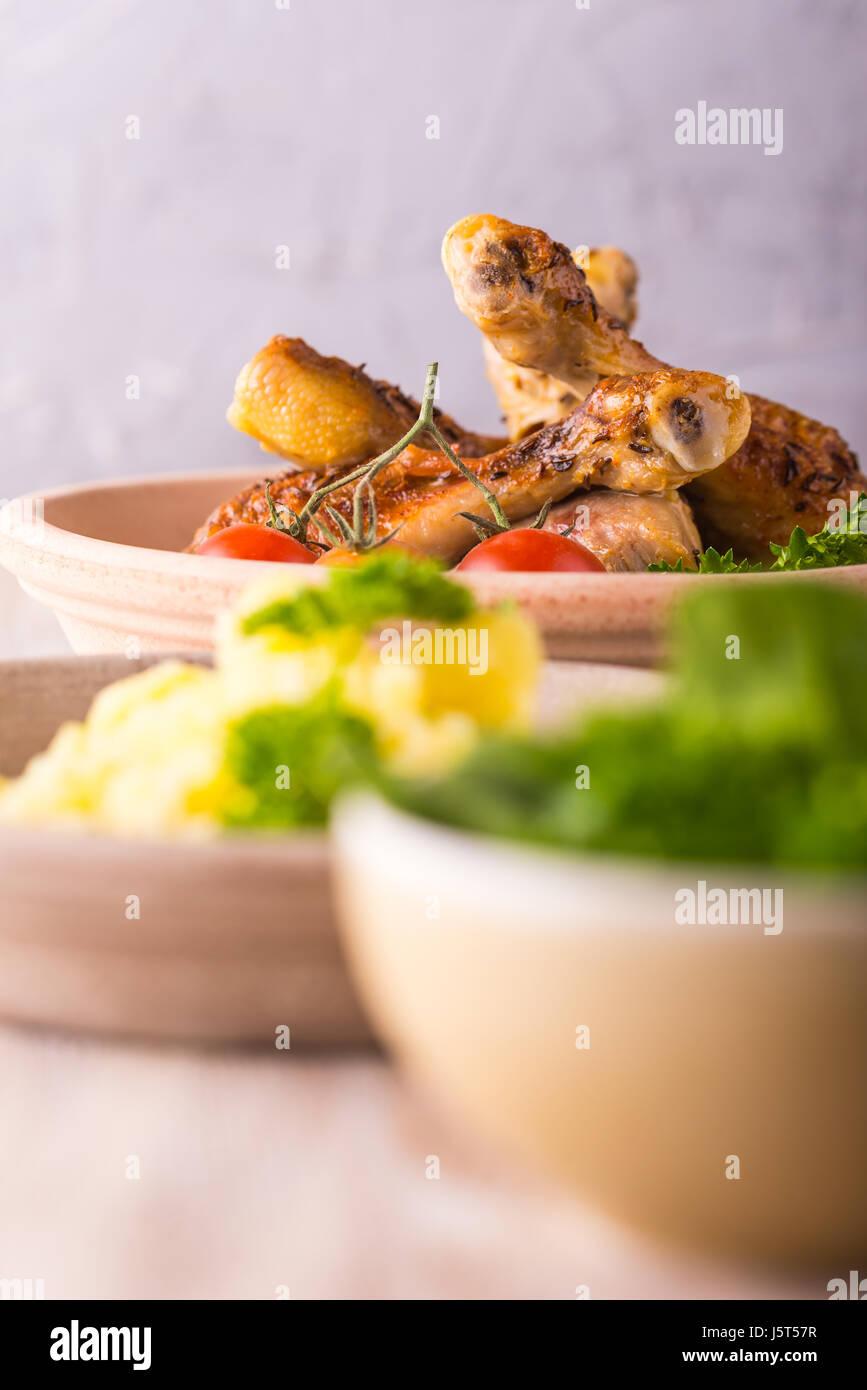 Vertikale Foto mit gebackene oder gebratene Hähnchenschenkel auf Ton Platte. Das Essen ist auf hölzernen Stockbild