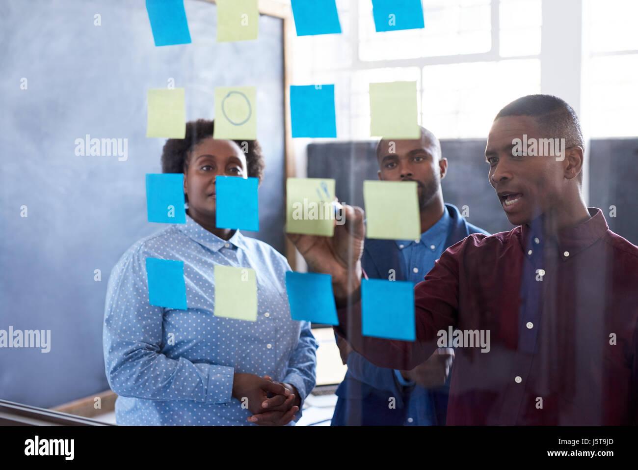 Afrikanische Unternehmer brainstorming mit Haftnotizen auf eine Glaswand Stockbild