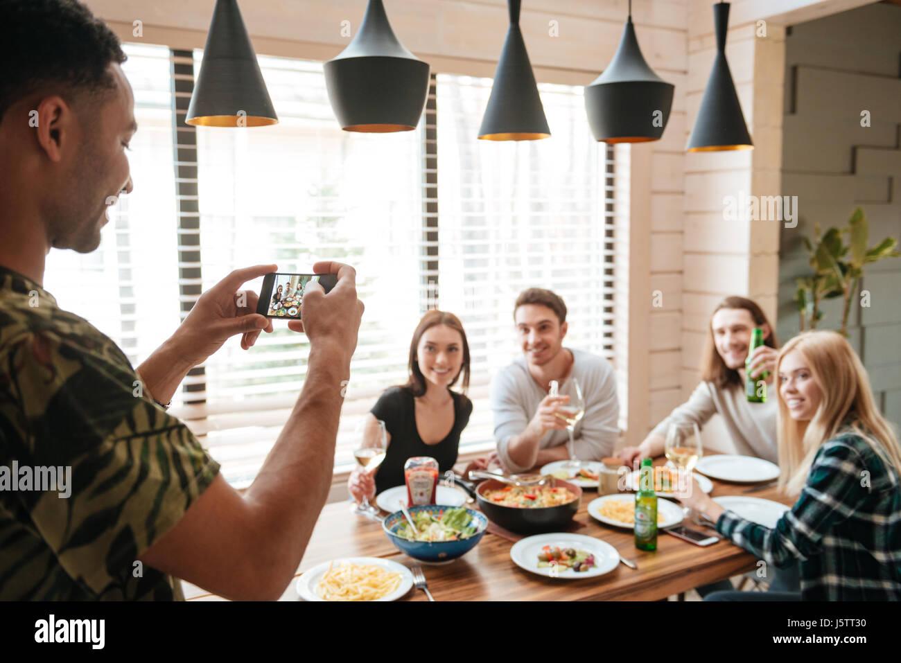 Glücklich Jüngling stehen und reden Fotos seiner Freunde mit Handy zu Hause Stockbild