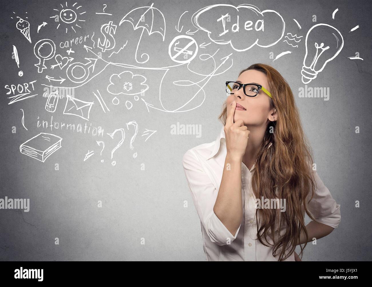 Porträt glückliche junge Frau denken träumen, hat viele Ideen, die isolierte graue Wand Hintergrund Stockbild