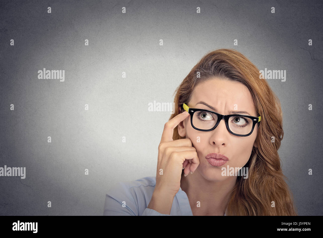 Kann mich nicht erinnern. Kopfschuss nachdenkliche junge Frau mit Brille schauen verwirrt isoliert graue Wand Background. Stockbild