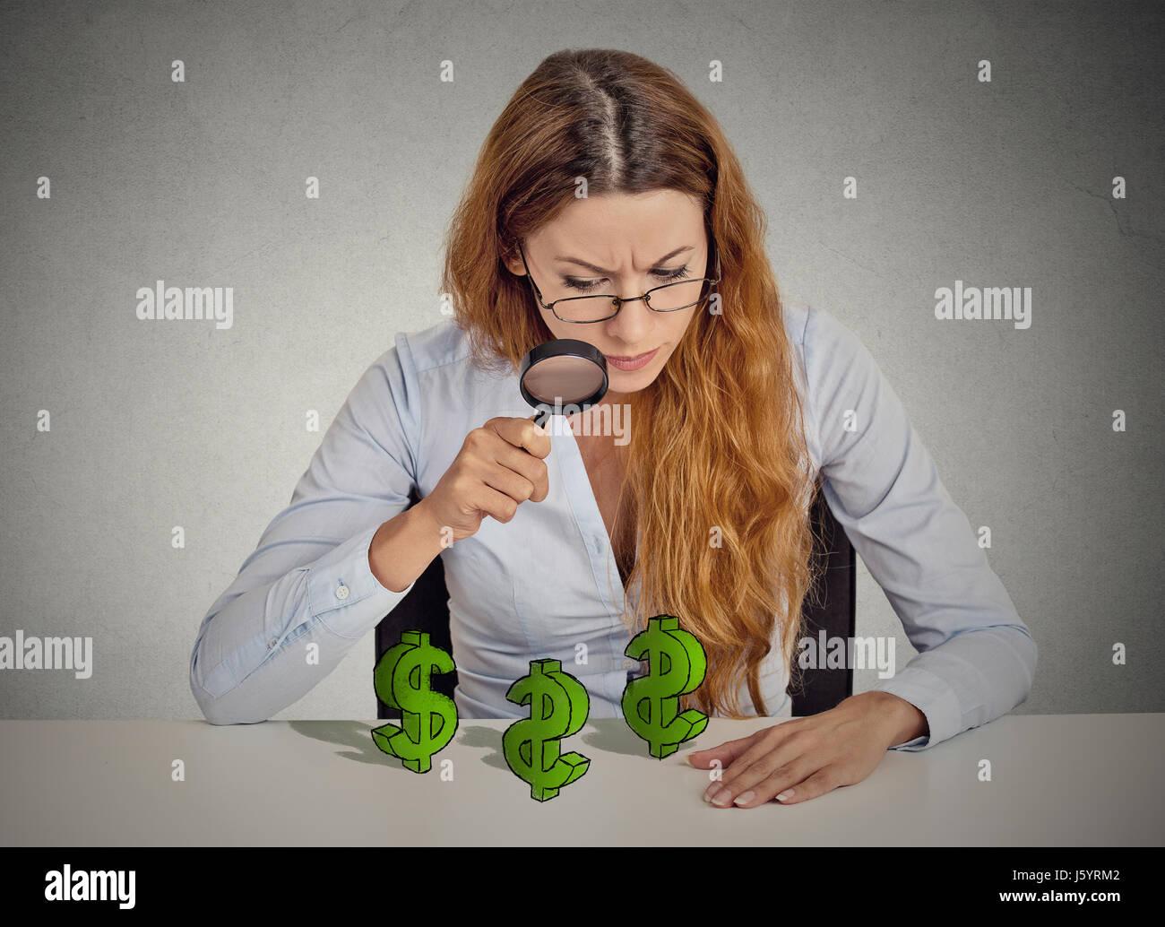 Pfennigfuchser. Geschäftsfrau, die Durchsicht Dollarzeichen Lupensymbol auf Tisch isoliert graue Wand Office Stockbild