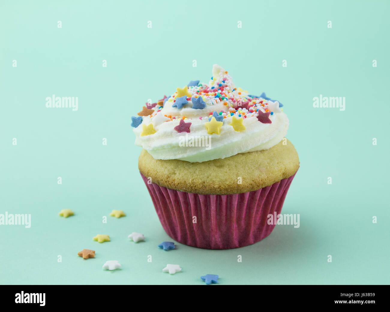 Ein Vanille Cupcake mit Wirbel weiße Glasur bestreut mit Sterne und Kugel Candy bunten Streuseln weichen grünen Stockbild