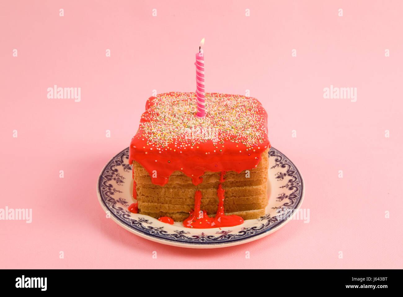 eine schrullige Vereisung Geburtstag Brot bedeckt mit Streuseln und rote Coulis auf rosa Hintergrund Stockbild