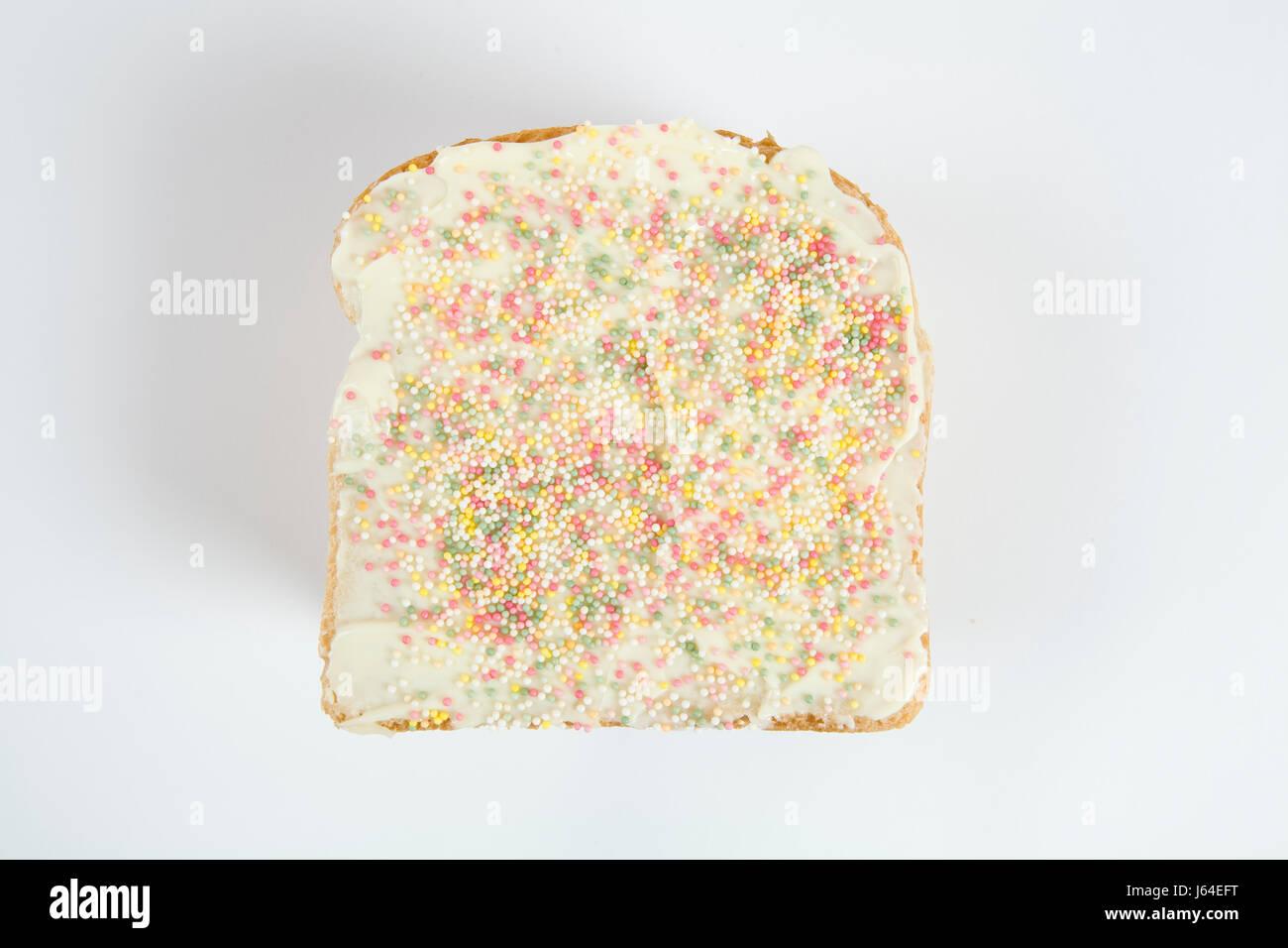 eine schrullige Vereisung Geburtstag Brot bedeckt mit Streuseln auf weißem Hintergrund Stockbild