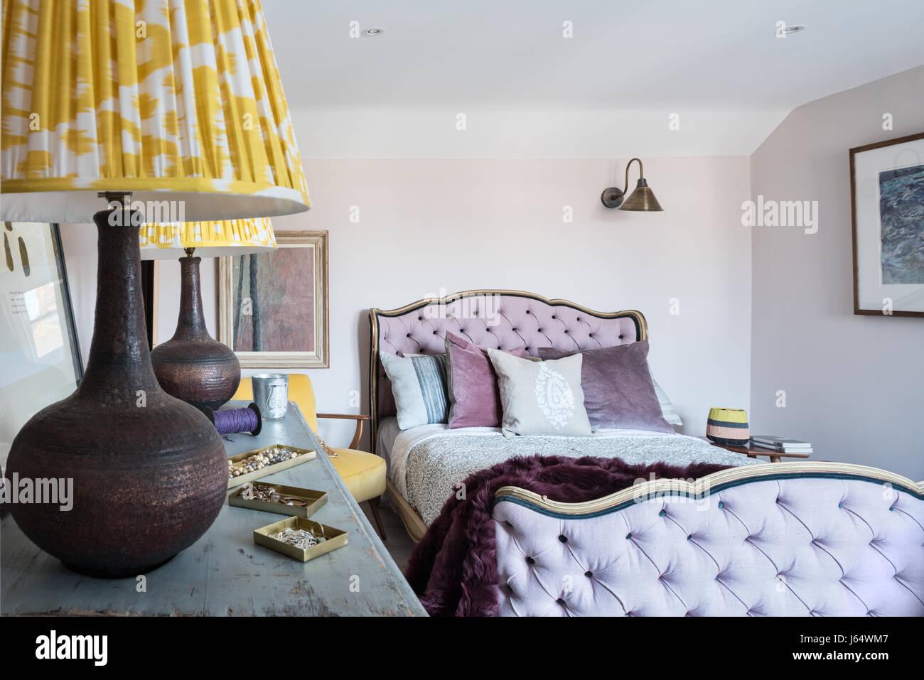 Lila Lammfell Wurf Auf Antikes Bett Mit Geknöpftem Kopfteil In Zimmer Mit  Zwei Gelben Ikat Print