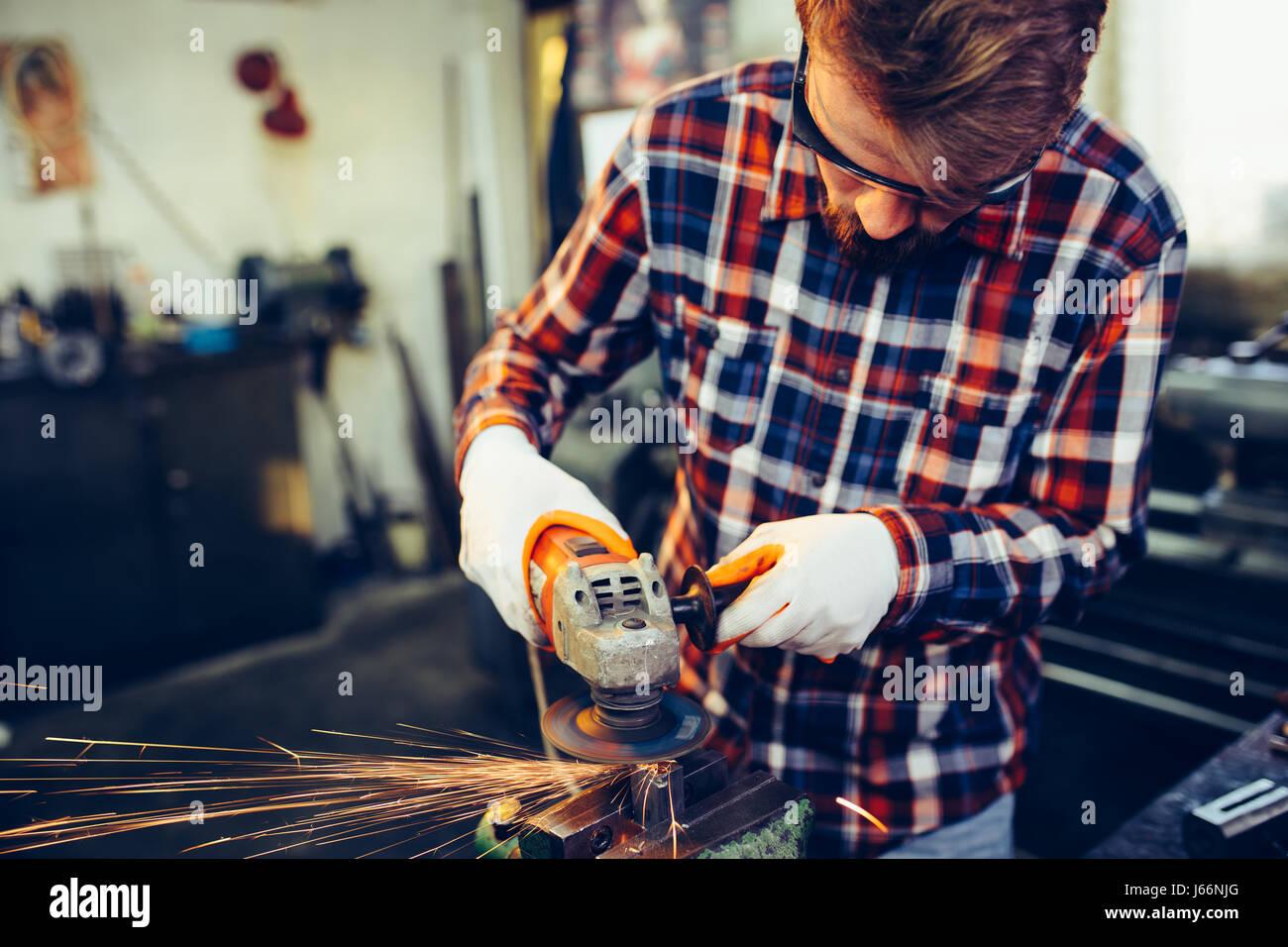 Junge Arbeiter arbeiten mit Mahlwerk Stockbild