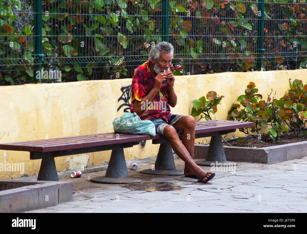 Ein Obdachloser Bettler auf einer Straße Bank in Playa Las Americas erholend zu fangen, während die wohlhabende Stockbild
