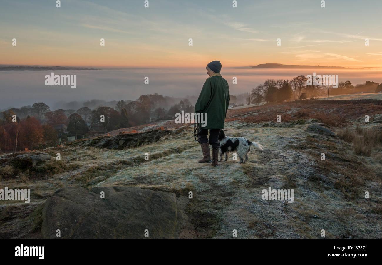 Frau wandern Hund auf einen Pfad auf Ilkley Moor an einem frostigen Morgen im Blick auf die Landschaft von einer Stockbild