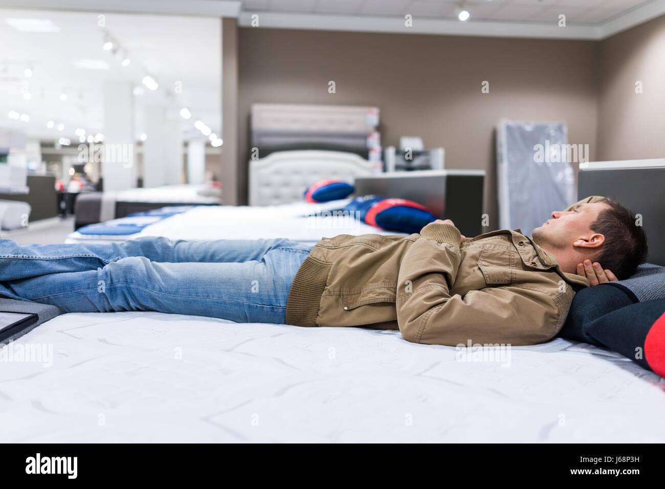 Junger Mann Festlegung auf Matratze auf dem Display im Store ausprobieren Stockbild