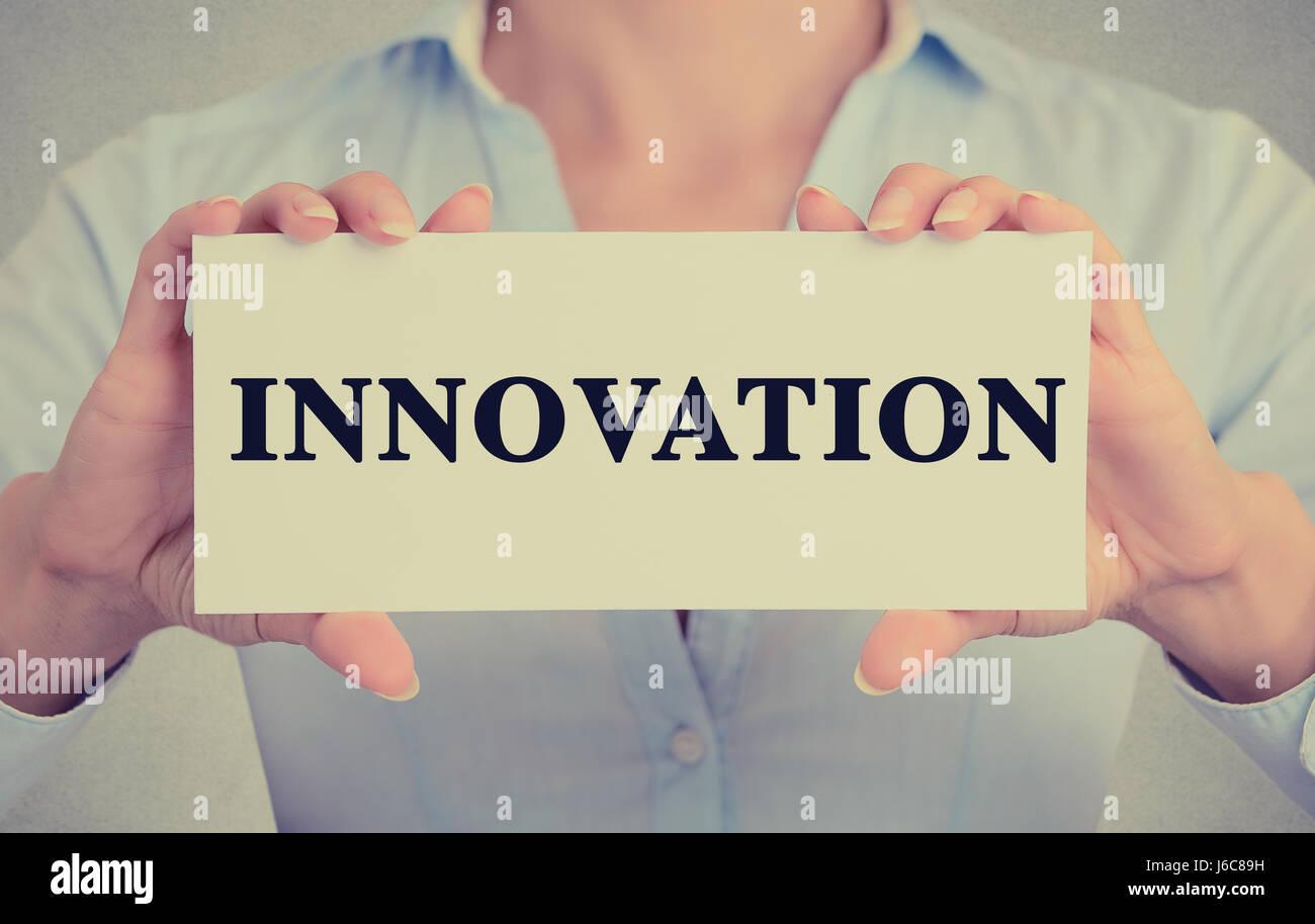 Closeup Geschäftsfrau Hände halten weiße Karte Zeichen mit Innovation Wort SMS auf graue Wand Büro Stockbild