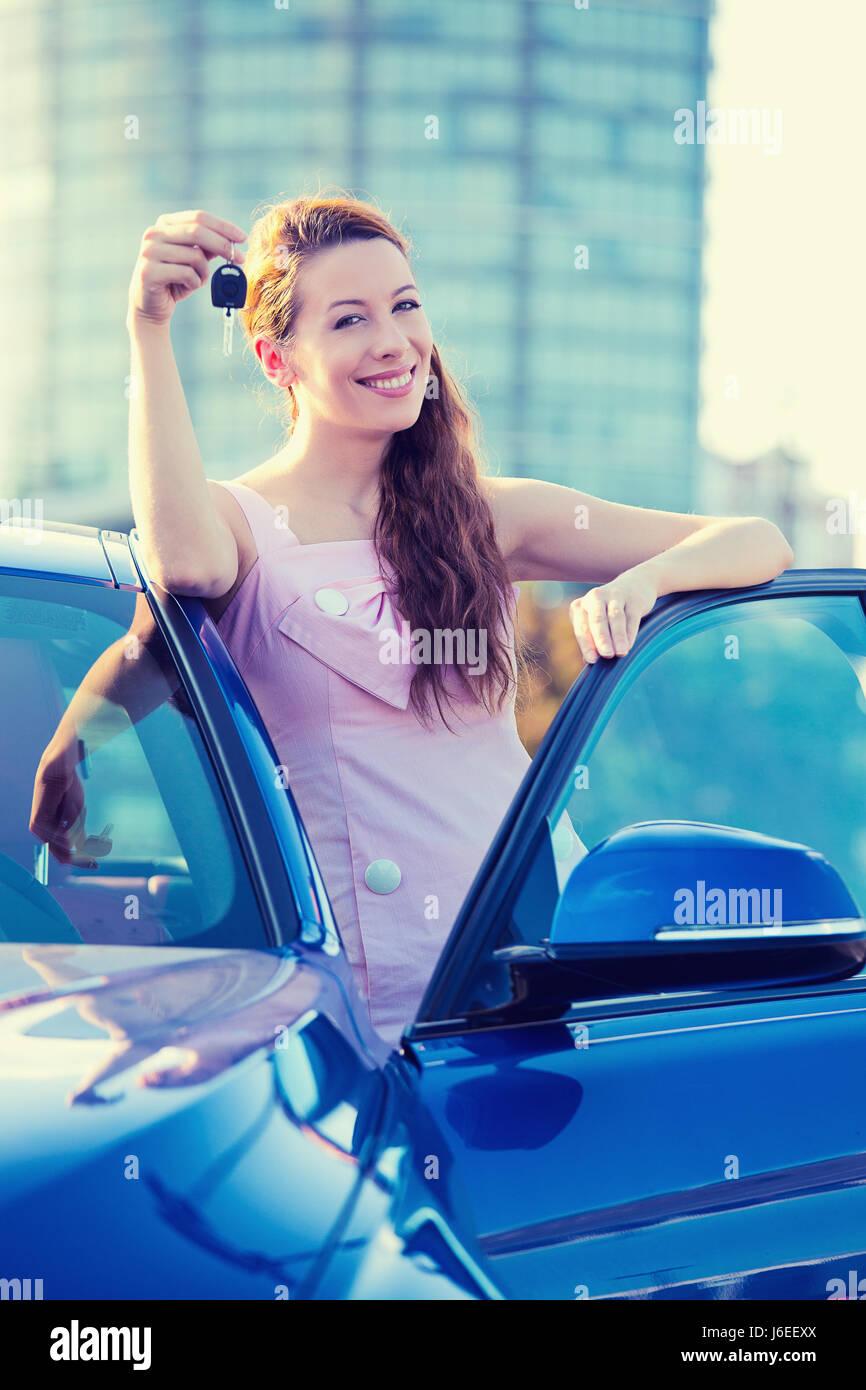 Porträt glücklich lächelnde junge attraktive Frau Käufer stehen neben neuen blaues Auto zeigen, Schlüssel isoliert Stockfoto