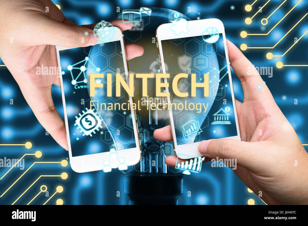 FinTech-Konzept. Zwei hand halten Mobiltelefon und Ikonen der Finanztechnologie. Glühbirne, Infografik, Texte Stockbild