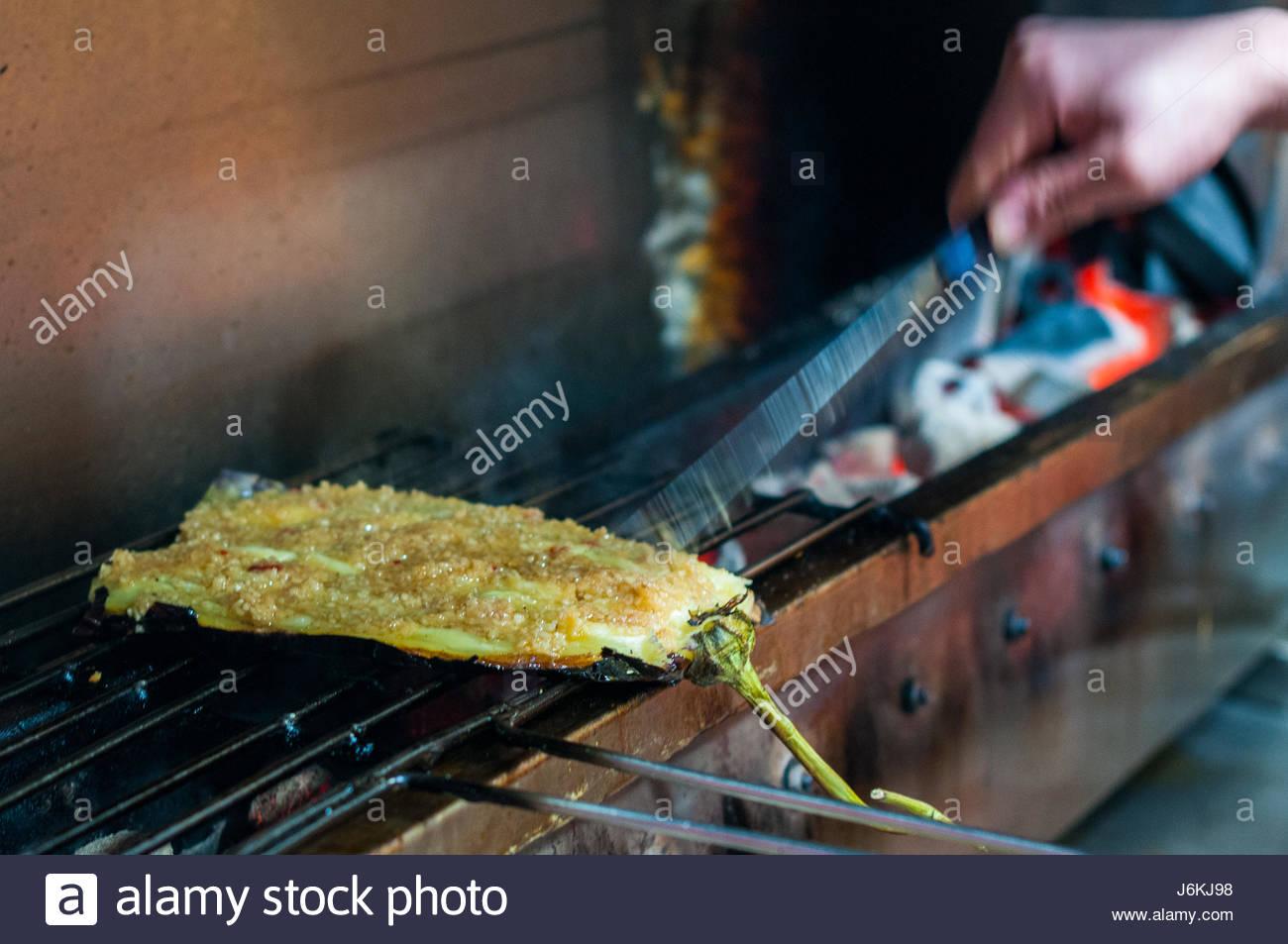eine aubergine, beladen mit knoblauch zubereitet auf dem grill vor