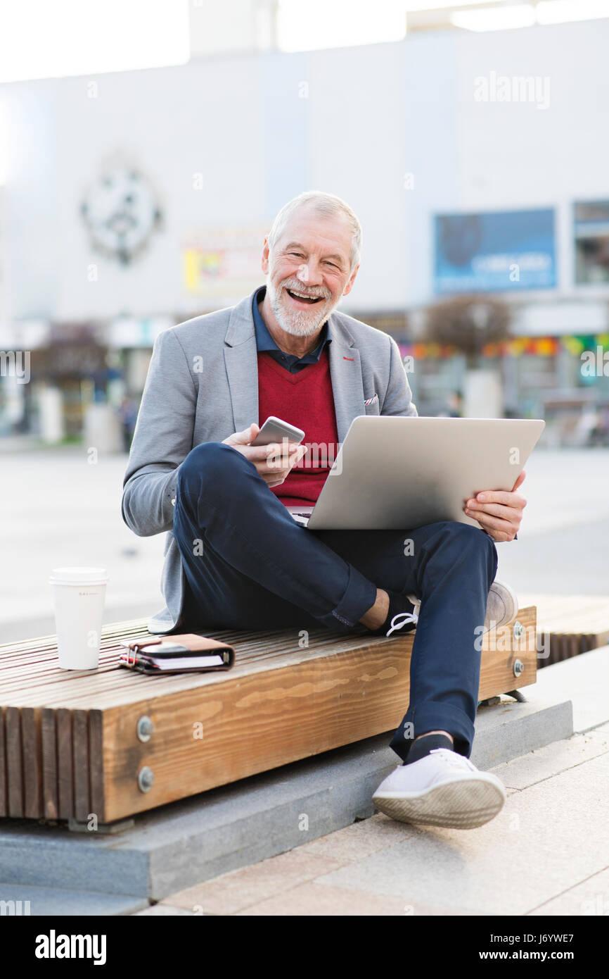 Ältere Mann in der Stadt mit Smartphone und laptop Stockbild