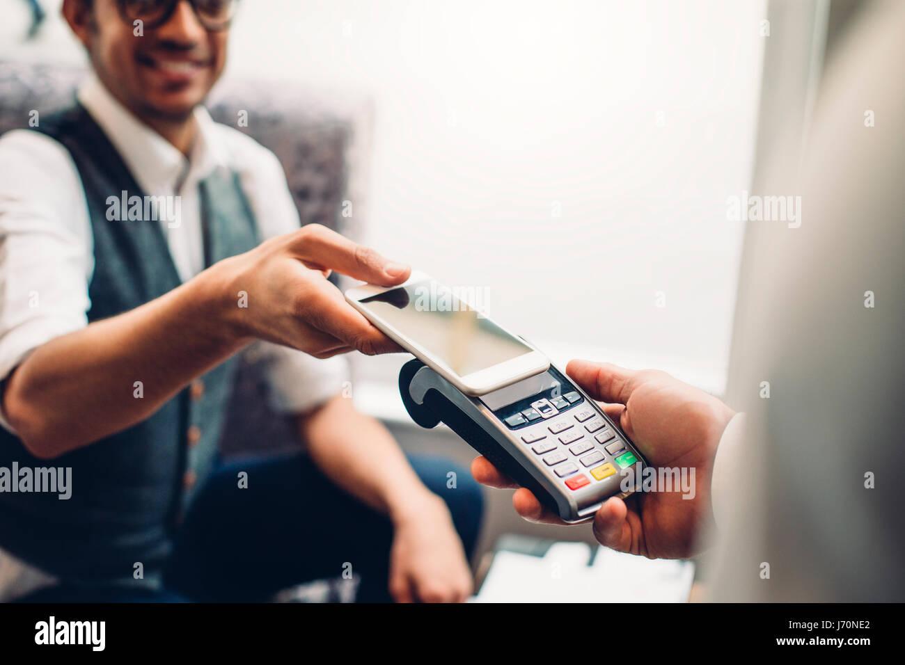 Business-Mann eine kontaktlose Smartphone Zahlung vornehmen. Stockfoto