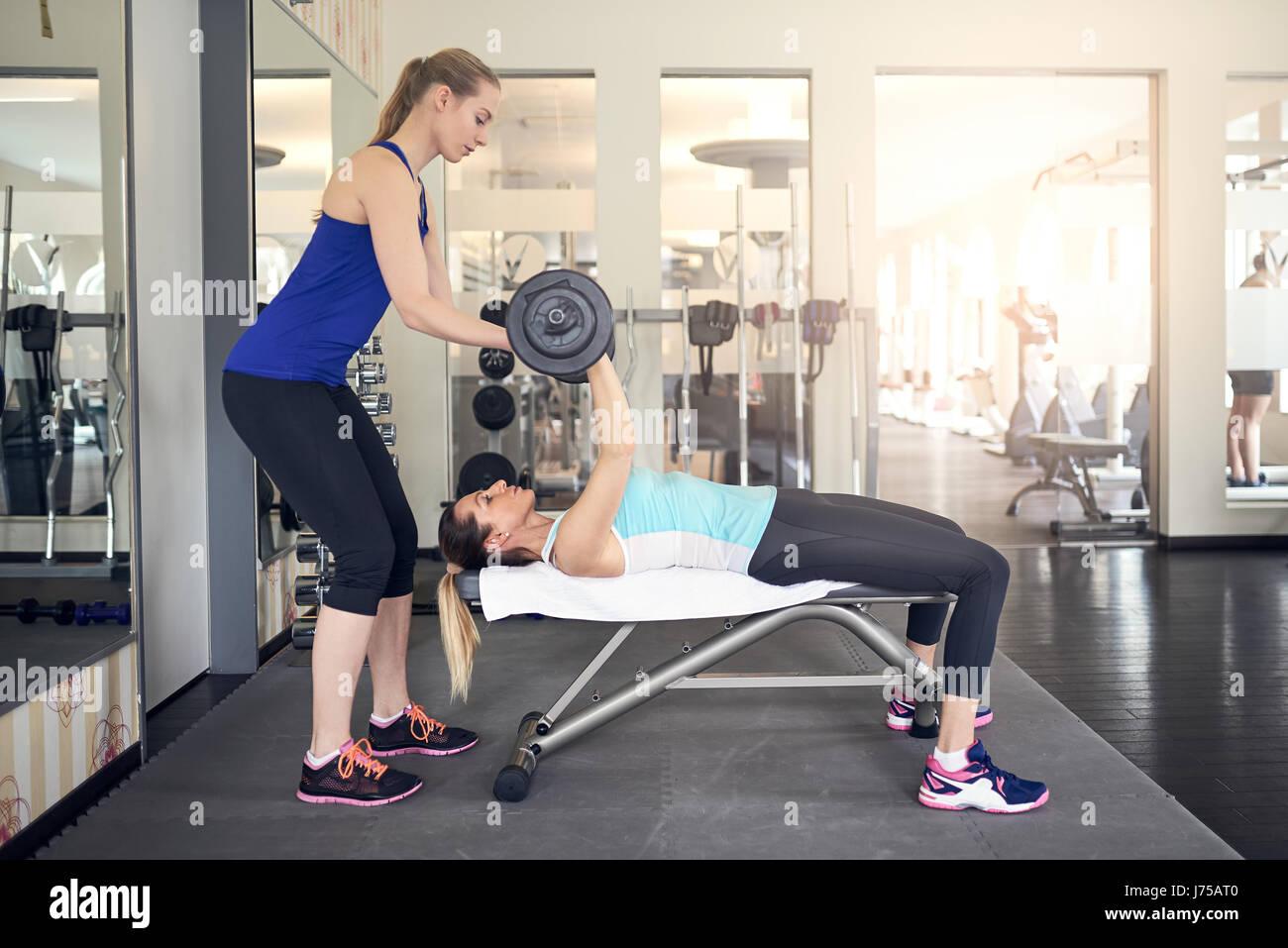 Junge Frau, die Arbeiten mit Langhantel Gewichte auf einer Bank in der Turnhalle mit Hilfe ihres personal Trainers Stockbild