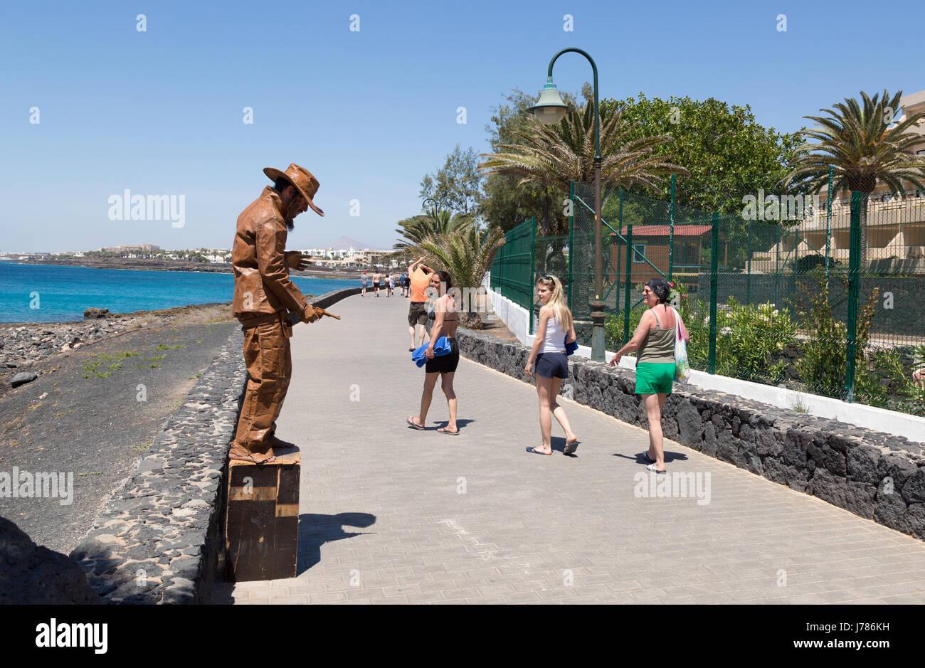 Lanzarote Urlaub - Touristen vorbei an einer Straße Entertainer, Avenida Los Cocederos, Costa Teguise, Lanzarote, Stockbild