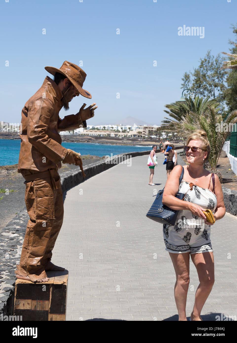 Ein Tourist, vorbei an einer Straße Entertainer, Avenida Los Cocederos, Costa Teguise, Lanzarote, Kanarische Stockbild