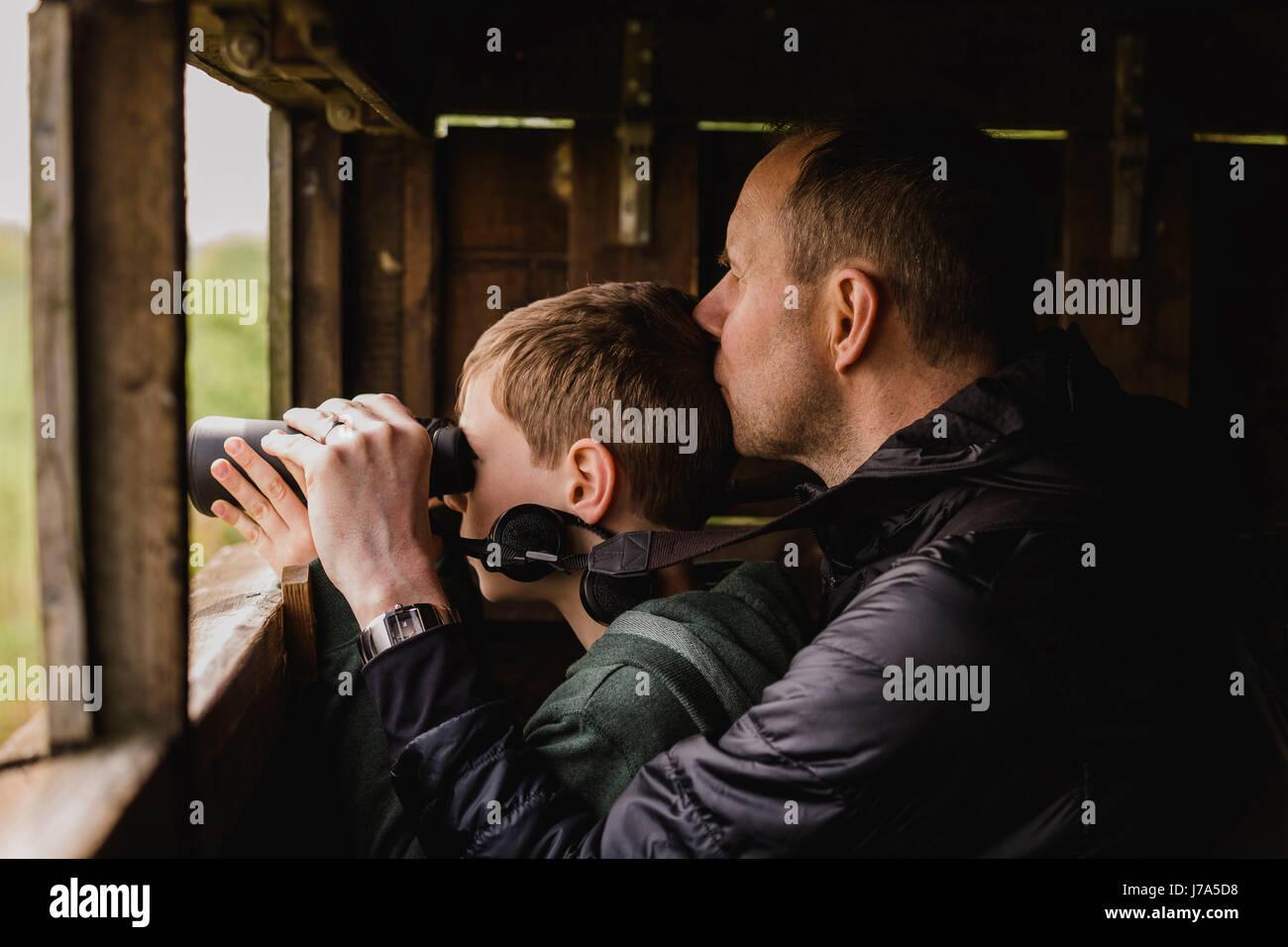 Junge und vater vogelbeobachtung mit dem fernglas stockfoto bild