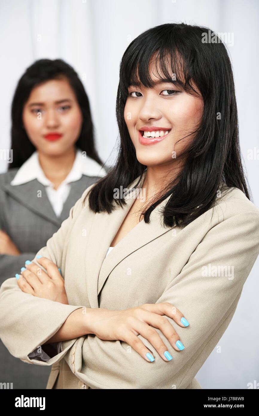 glücklich Geschäftsfrauen in Anzügen stehen und Gelenkarme Stockbild