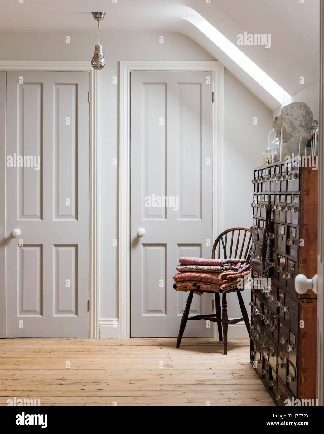 antike apothekerschrank in zimmer mit holzdielen und windsor stuhl die schrankt ren sind. Black Bedroom Furniture Sets. Home Design Ideas
