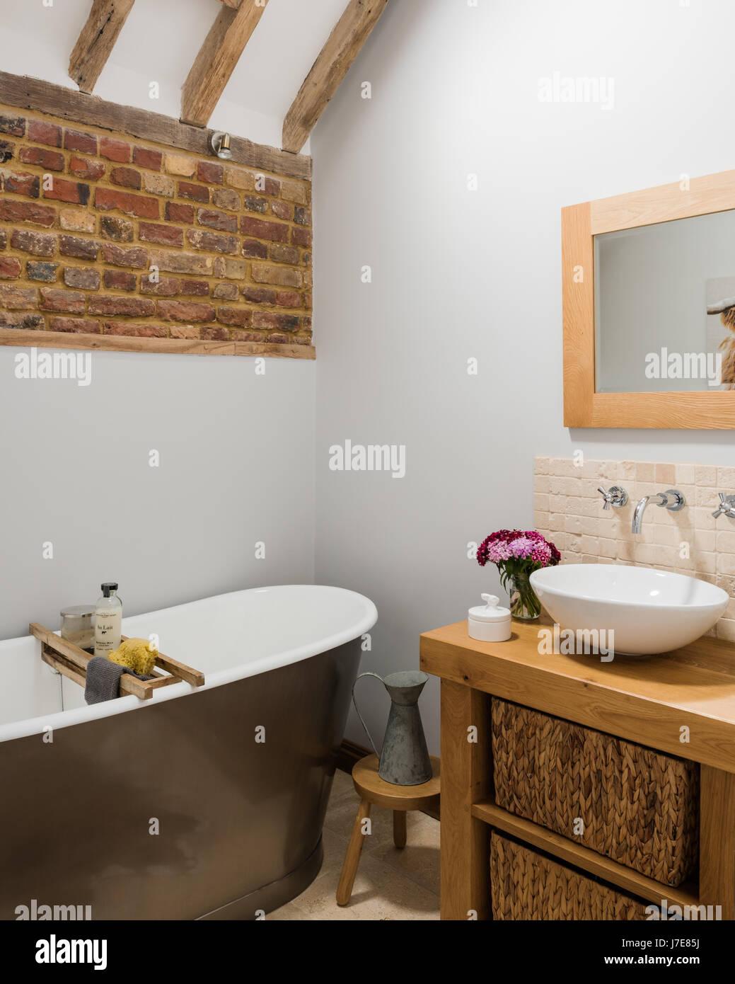 Freistehende Badewanne im rustikalen Badezimmer mit freiliegenden ...