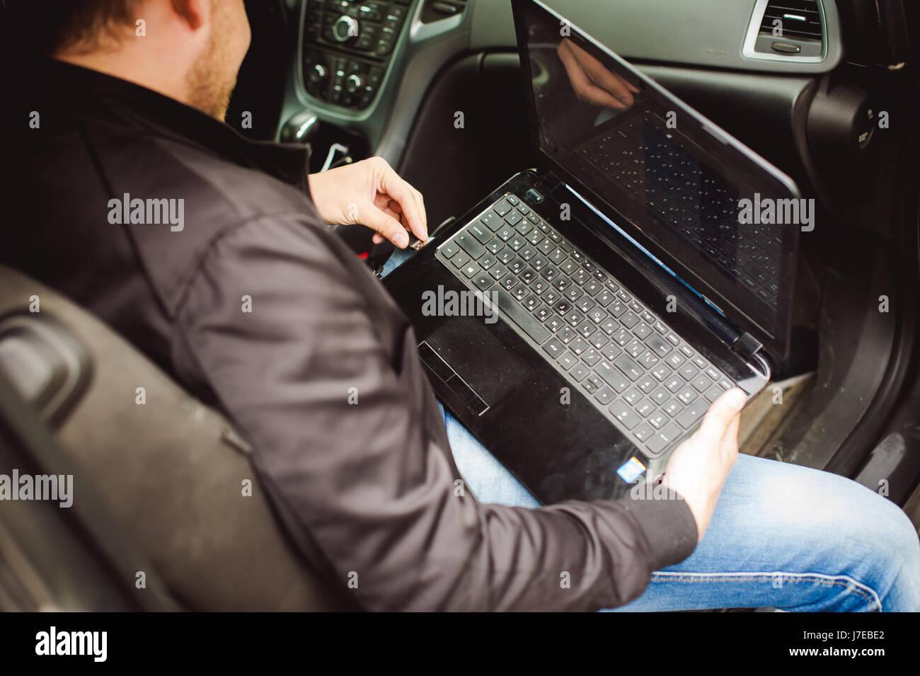 Professionelle Mann mit Laptop im Auto tunes tuning Control-System ...