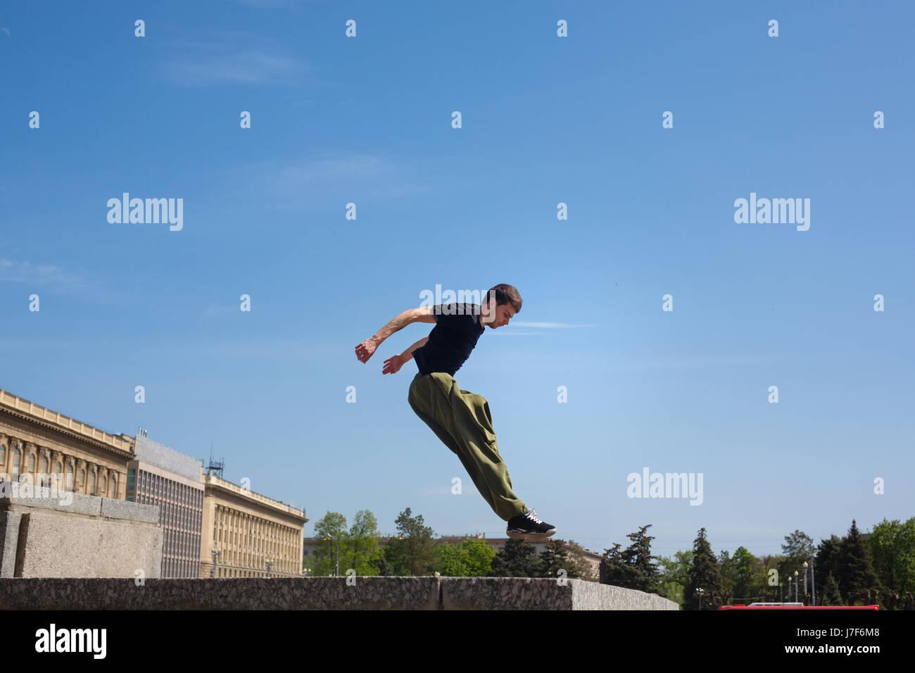 Junger Mann springt an die Wand. Parkour im urbanen Raum. Sport in der Stadt. Sportliche Aktivität. Stockbild