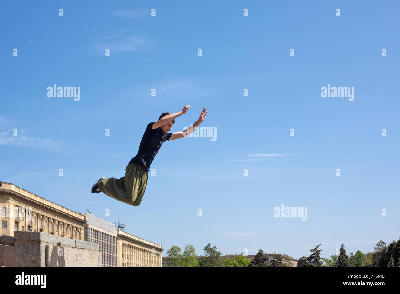 Ein junger Mann springt von der Wand. Parkour im urbanen Raum. Sport in der Stadt. Sportliche Aktivität. Stockbild