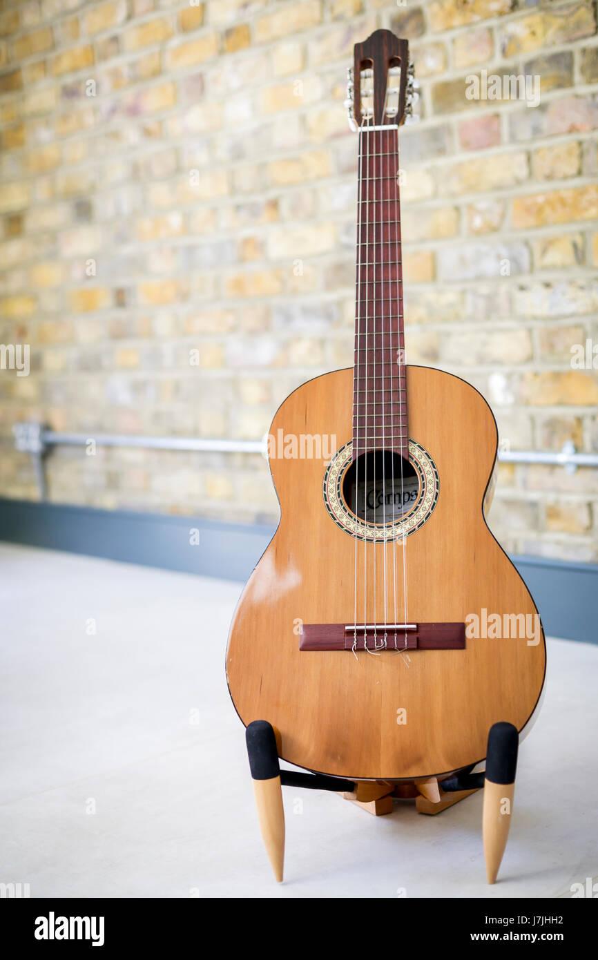 6-saitigen Gitarre auf einem Ständer, gegen innere Mauer mit industrielle elektrische Leitung Stockbild