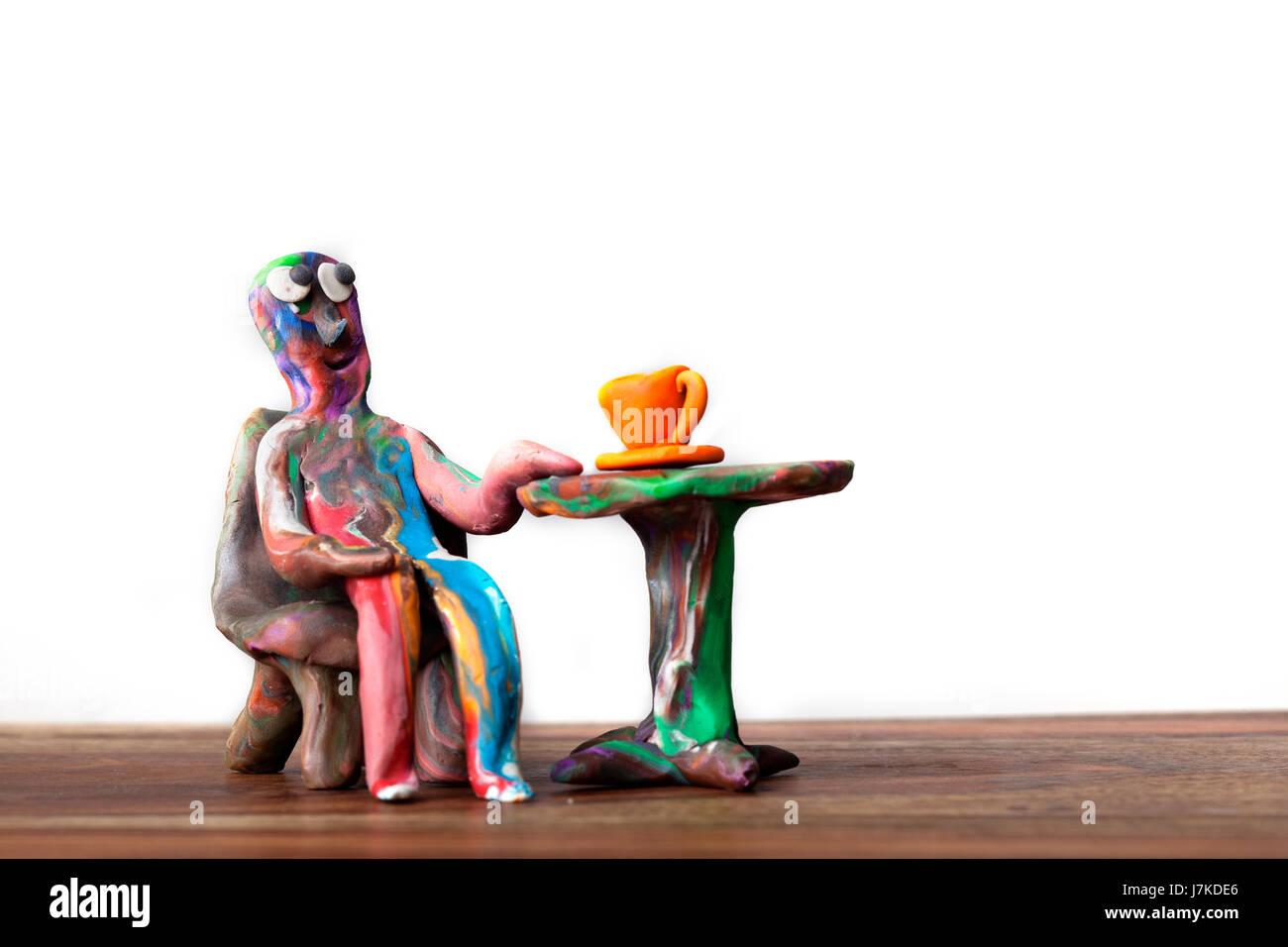 kleine winzige kleine kurze Mini männlich Miniatur kneten Aussehen Mann Café Tasse braun Stockfoto