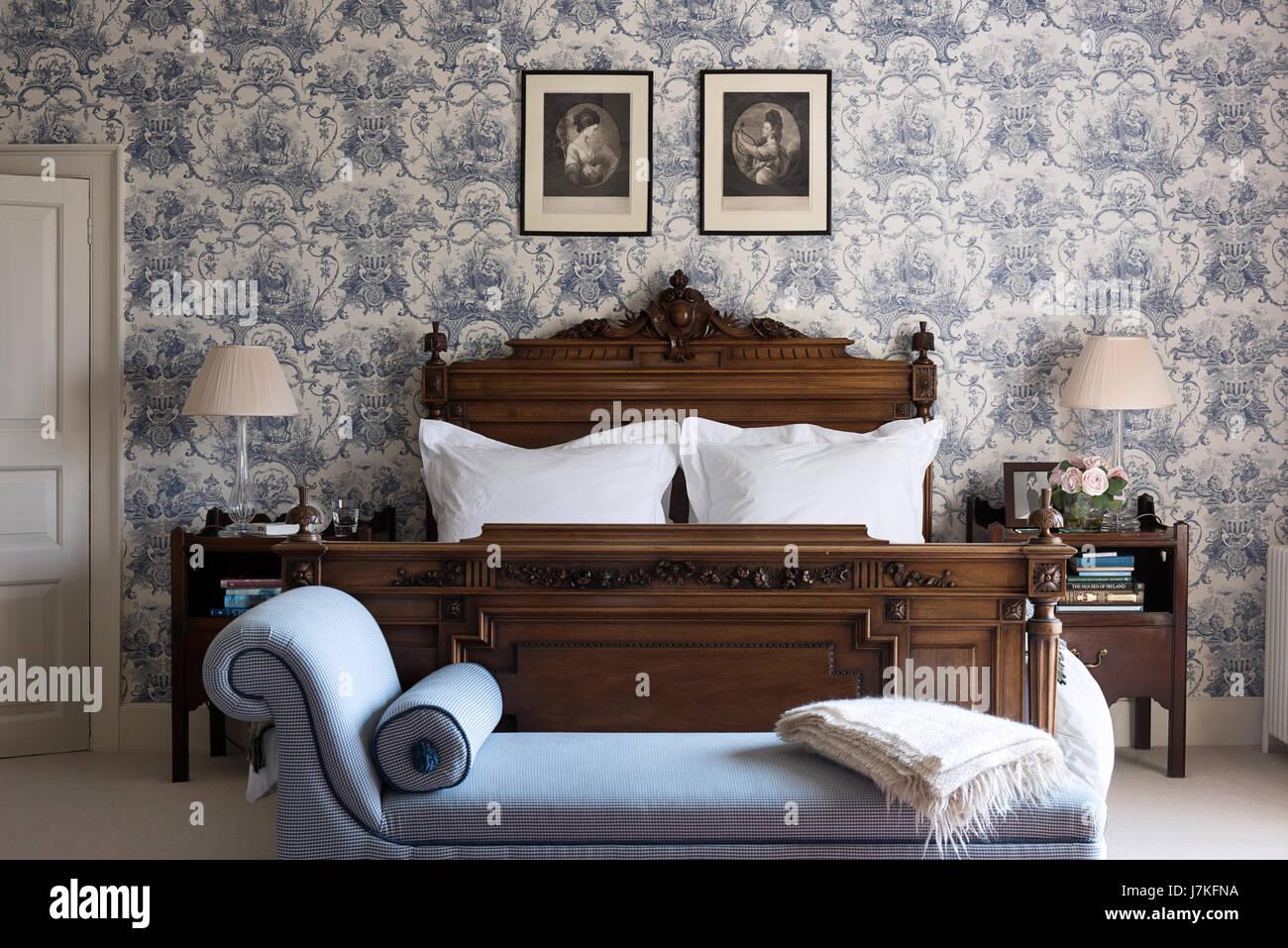 Chaiselongue am Fuße des ein antikes Holz Bett im ...