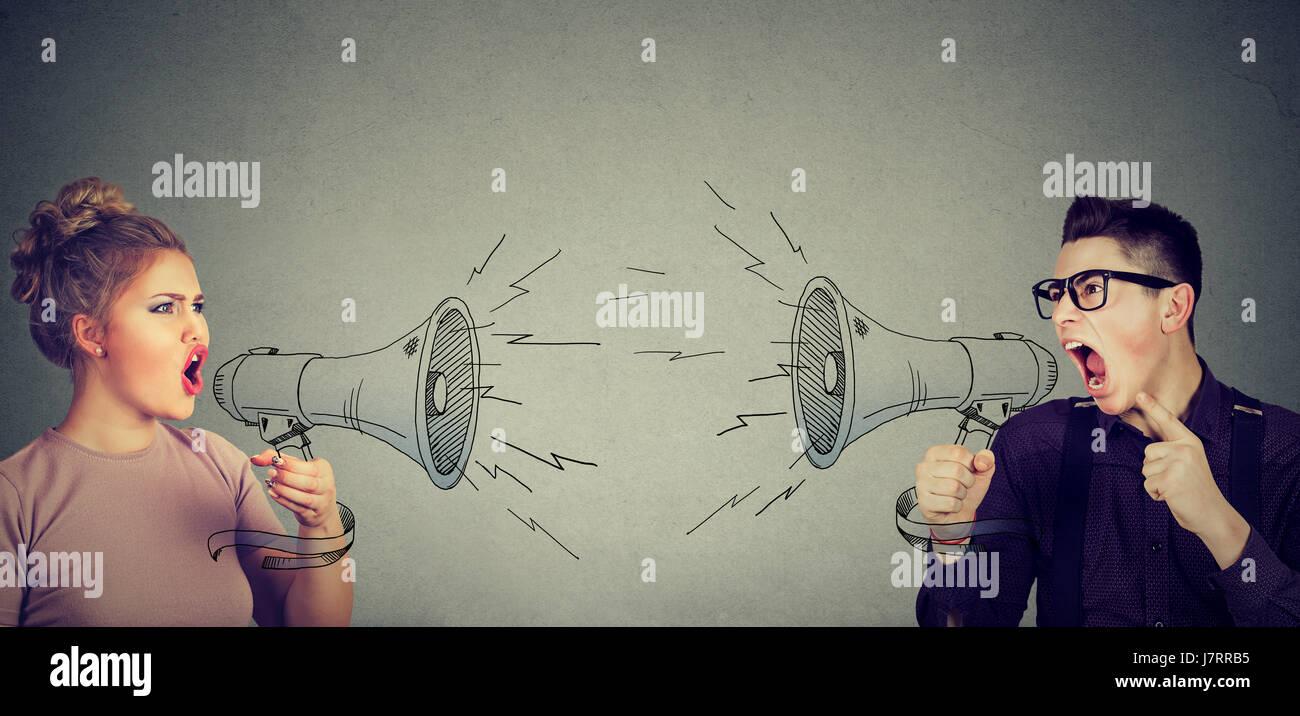 Streit zwischen Frau und Mann schreien sich gegenseitig im Megaphon Stockbild