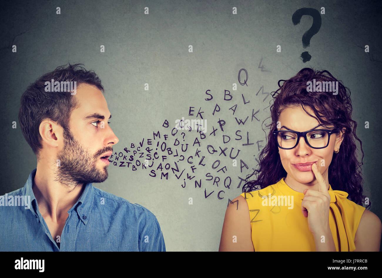 Sprache-Barriere-Konzept. Gutaussehenden Mann im Gespräch mit einer attraktiven jungen Frau mit Fragezeichen Stockbild