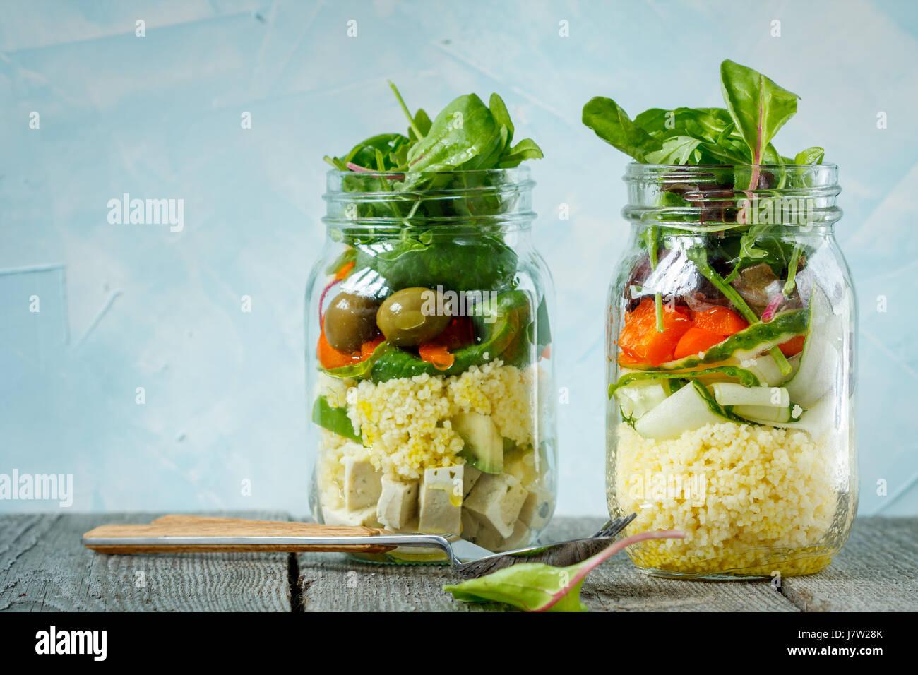 Bunter Salat mit Couscous, Tofu und Gemüse im Glas. Liebe für eine gesunde vegane Ernährung Konzept Stockbild