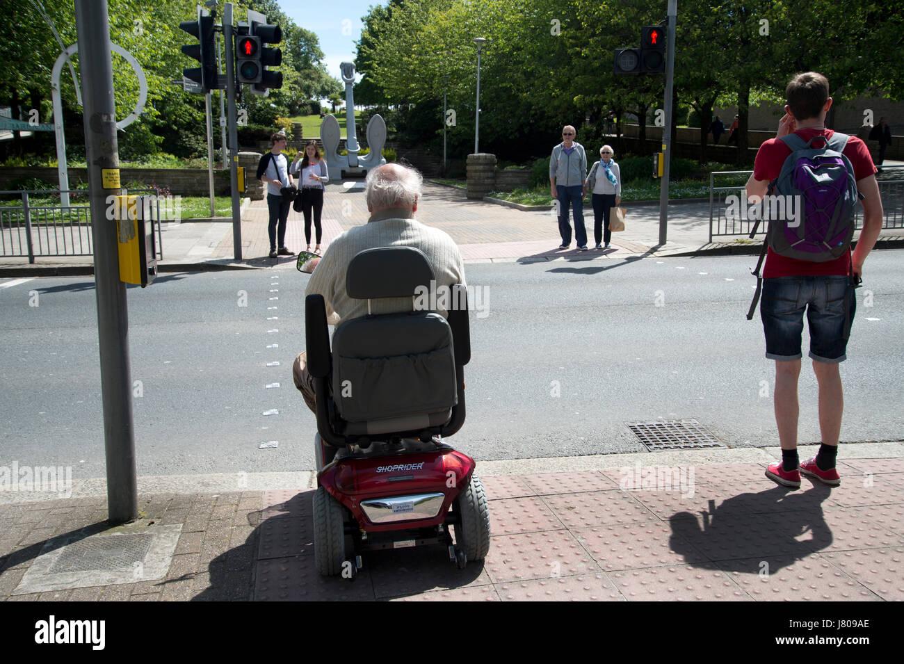 Plymouth, Devon. Menschen, darunter einen älteren Mann mit einer Behinderung-Roller warten, um eine Straße Stockbild