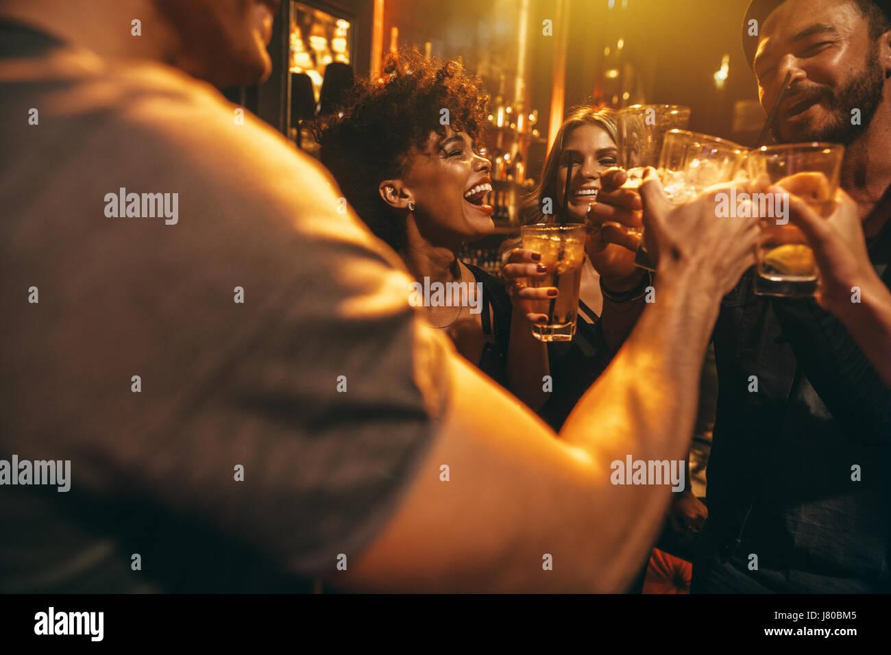 Glücklichen Gruppe von Menschen genießen Drinks an Bar. Junge Freunde im Nachtclub Toasten Cocktails. Stockbild